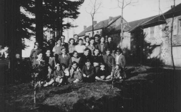 <p>Enfants juifs accueillis à la Maison des Roches, le foyer pour enfants dirigé par Daniel Trocmé (derrière au centre, portant des lunettes). Le Chambon-sur-Lignon, France, entre 1941 et 1943.</p>