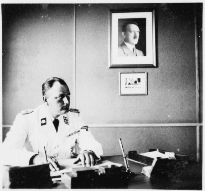 The commander of Gross-Rosen, SS-Obersturmbannfuehrer Arthur Roedl, at his desk with a photograph of Adolf Hitler hanging on the wall.