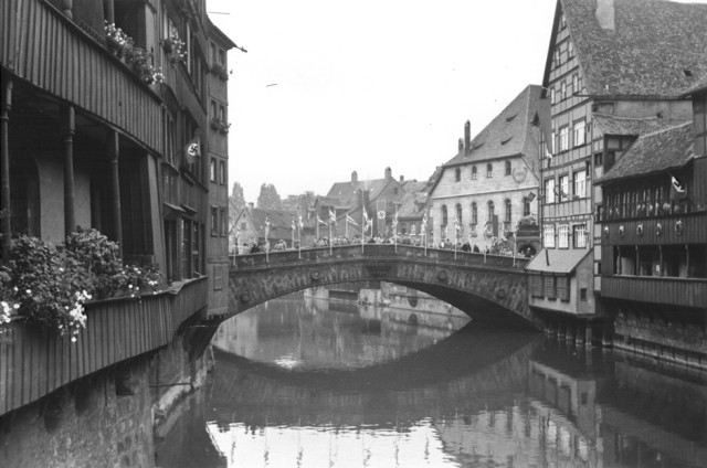 View of a bridge spanning a canal in Nuremberg. The houses and bridge are bedecked with Nazi flags and banners. [LCID: 64447]