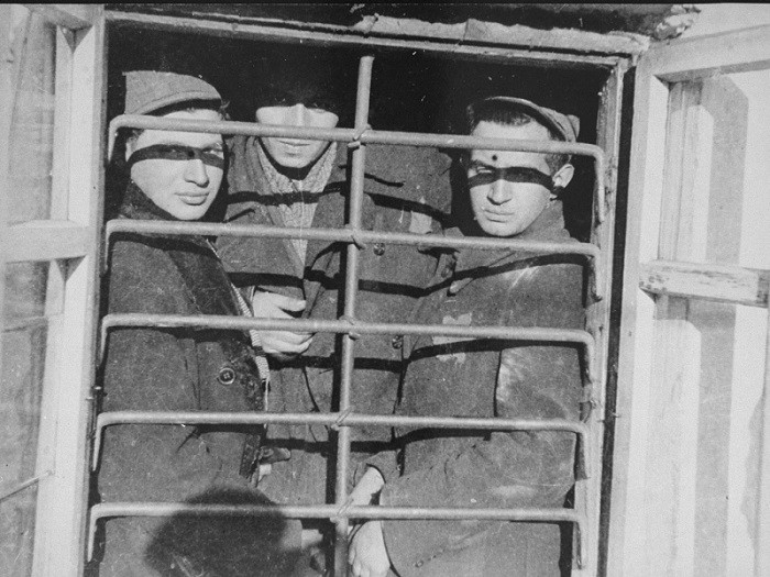 Scene photographed by George Kadish: Jewish prisoners behind a barred window in the Kovno ghetto jail. [LCID: 81155]