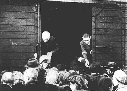 Jews being deported from the Warsaw ghetto board a freight train. [LCID: 05533]