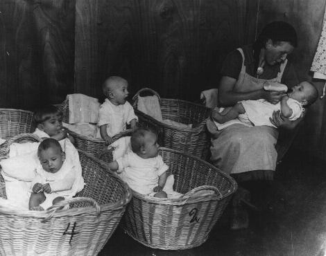 "<p>German propaganda photograph of a kindergarten for German infants promotes the nurturing role of <a href=""/narrative/4164"">women</a> on the home front. Germany, 1941.</p>"