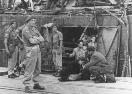 """An exhausted Jewish woman from the """"Exodus 1947"""" refugee ship is given a drink as British soldiers stand nearby. [LCID: 69776]"""