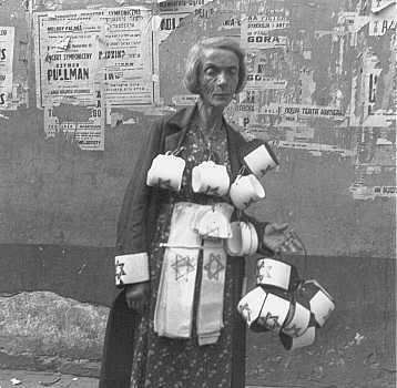 An emaciated woman sells the compulsory Star of David armbands for Jews. [LCID: 32298]