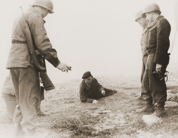 "<p>Bonde Gaza, a Hungarian musician who survived the <a href=""/narrative/8101/en"">Gardelegen</a> atrocity, demonstrates to American soldiers how he managed to escape from the barn which the SS had set on fire. Germany, April 14–18, 1945.</p>"