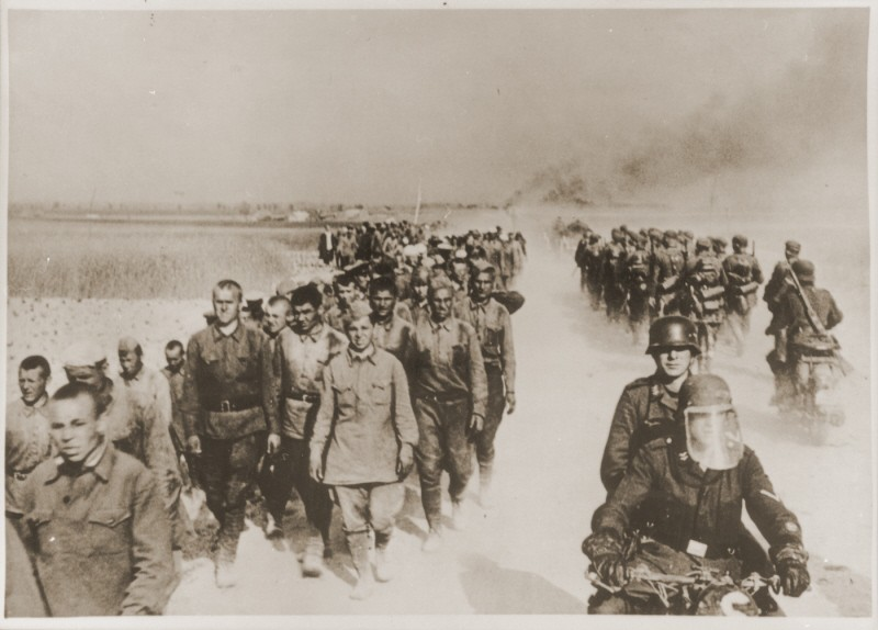 At left, a column of Soviet prisoners of war, under German guard, marches away from the front. [LCID: 76154]