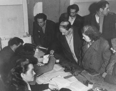 <p>Checking identity cards of Jews who fled eastern Europe after the war (as part of the Brihah), in preparation for the journey to Palestine. Photograph taken by Henry Ries. Vienna, Austria, November 5-6, 1947.</p>