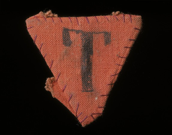"""<p>Parche triangular rojo que debía usar el prisionero político checo Karel Bruml en Theresienstadt. La letra """"T"""" significa """"Tscheche"""" (""""checo"""", en alemán).</p>"""