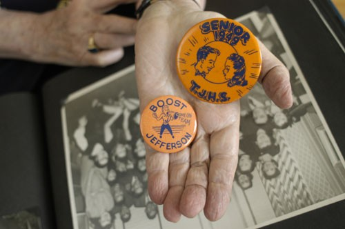 Regina Gelb holds buttons from her high school days. [LCID: athrg504]