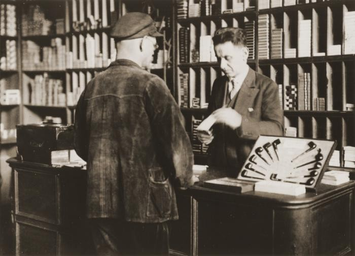 Arthur Lewy with a customer in his tobacco shop in Berlin. Arthur was arrested in 1938 and was forced to sell his business after his release. Berlin, Germany, 1938.