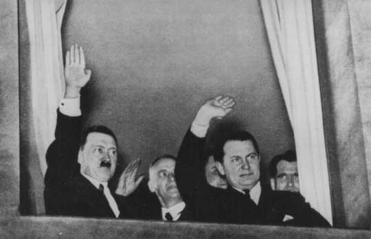 Adolf Hitler, Wilhelm Frick, and Hermann Goering wave to a torchlight parade in honor of Hitler's appointment as chancellor. [LCID: 79869]