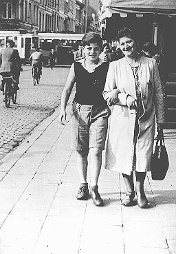 """<p>Shoshane Varmel Levy and her son, Jules, wearing the <a href=""""/narrative/11750"""">compulsory yellow badge</a>, on a street in Antwerp. Belgium, June 1942.</p>"""