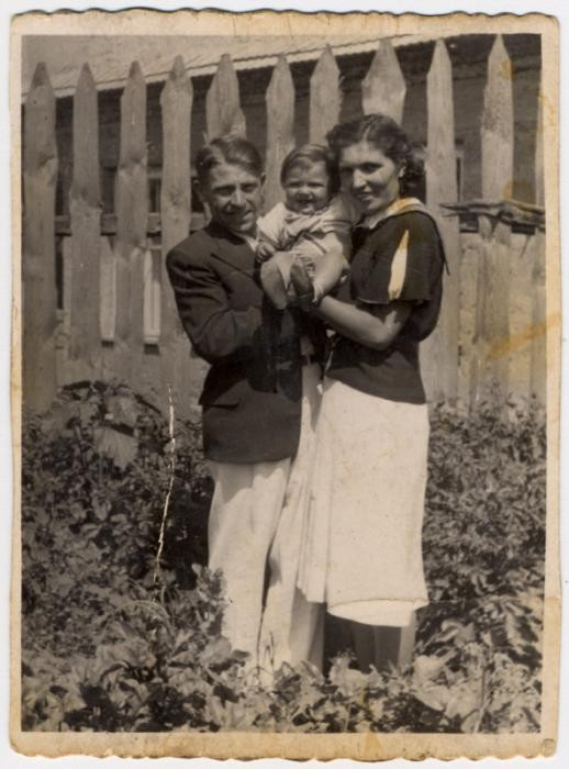 <p>Shlamke and Shanke Minuskin pose with their baby son, Henikel, in the garden of their home. Zhetel, Poland, 1938.</p>
