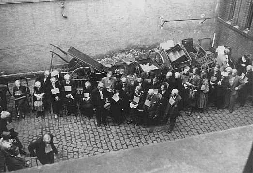 <p>یهودیان آلمانی با کارت های شناسایی، پیش از تبعید به ترزین اشتاد. ویزنبادن، آلمان، اوت 1942.</p>
