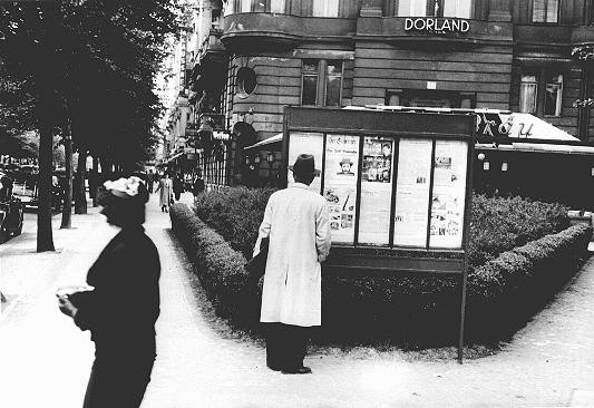 "A pedestrian stops to read an issue of the antisemitic newspaper ""Der Stuermer"" (The Attacker) in a Berlin display box. [LCID: 02629]"