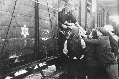 Jews load a barrel of water onto a deportation train in Skopje.