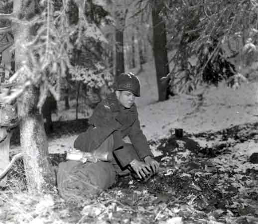A soldier prepares to bed down for the night in a Belgian forest during the Battle of the Bulge. [LCID: sc110]