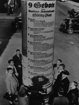 """<p>German pedestrians read Hermann Goering's """"Nine Commandments for the Workers' Struggle,"""" which included such exhortations as this one to German women: """"take hold of the frying pan, dust pan and broom and marry a man."""" Berlin, Germany, May 1934.</p>"""