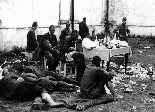 """<p>Wounded <a href=""""/narrative/10135"""">Soviet prisoners of war</a>await medical attention. The German army provided only minimal treatment, and permitted captured Soviet personnel to care for their own wounded using only captured medical supplies. Baranovichi, Poland, wartime.</p>"""
