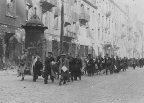 Jews rounded up during the Warsaw ghetto uprising are forced to march to the assembly point for deportation. [LCID: 34082]