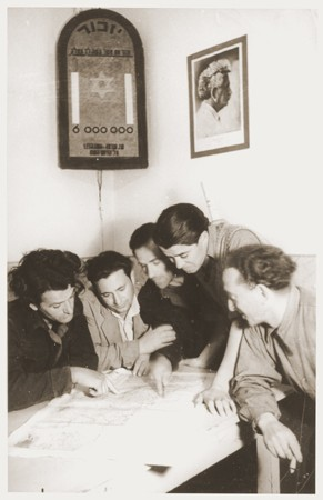<p>Members of Kibbutz Nili (a Zionist agricultural collective) study a map of Palestine. Above them hangs a wall plaque memorializing the six million Jews killed during the Holocaust. On the other wall is a photograph of the Labor Zionist leader, Berl Katznelson. Pleikershof, Germany, 1945-1948.</p>