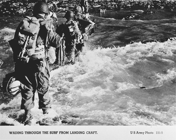American troops wade through the surf on their arrival at the Normandy beaches on D-Day. [LCID: 65995]
