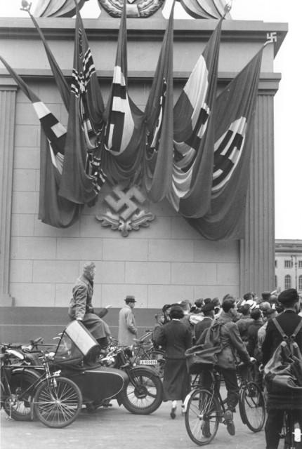 <p>Espectadores alemães de um comício nazista parados ao lado de um monumento decorado com bandeiras nazistas e o emblema da suástica. Berlim, Alemanha. 1937.</p>