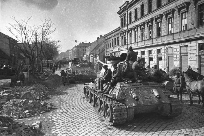 Soviet tanks roll down a street in Vienna