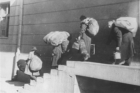 A family of Macedonian Jews carries their luggage down a flight of stairs as they leave the Tobacco Monopoly transit camp for the deportation trains.