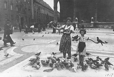 Berta and Inge Engelhard play with the pigeons in fron of the Feldherrenhalle in Munich. [LCID: 99683]