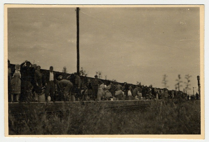 Displaced persons stand on a train platform in the weeks after the end of World War II in Europe.
