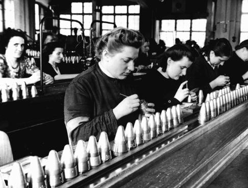 Women at work in Germany's armaments industry. The women in front are forced laborers brought in from a nearby prison.