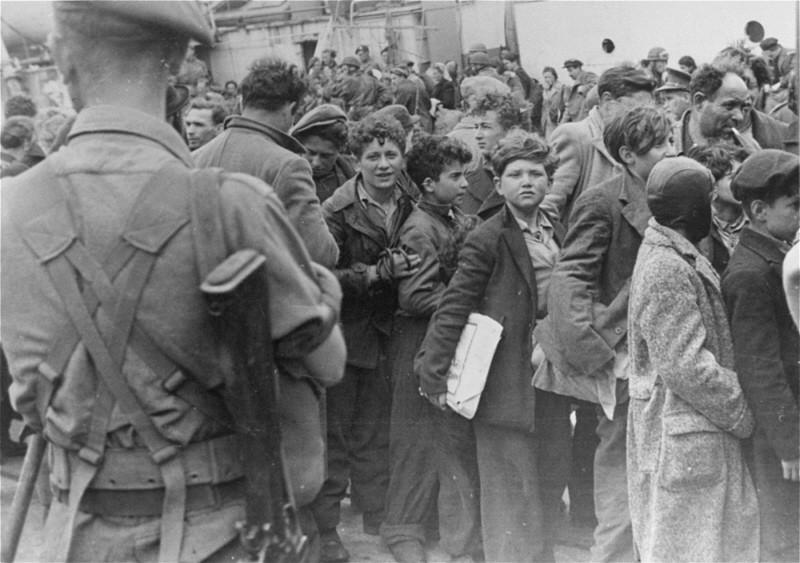 """<p>Des soldats britanniques transfèrent des enfants réfugiés du """"Théodore Herzl"""", un bateau de l'Aliyah Beit (immigration clandestine) sur un autre navire pour être déportés dans des camps de détention à Chypre. Port de Haïfa, Palestine, 24 avril 1947.</p>"""