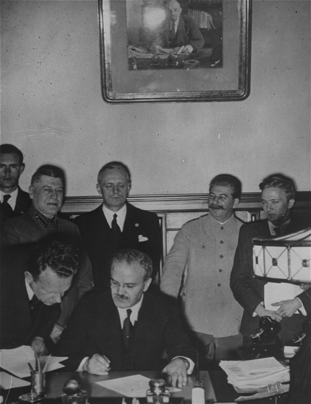 <p>Soviet foreign minister Viacheslav Molotov signs the German-Soviet pact as Soviet leader Joseph Stalin (white uniform) and German foreign minister Joachim von Ribbentrop (behind Molotov) look on. Moscow, Soviet Union, August 23, 1939.</p>