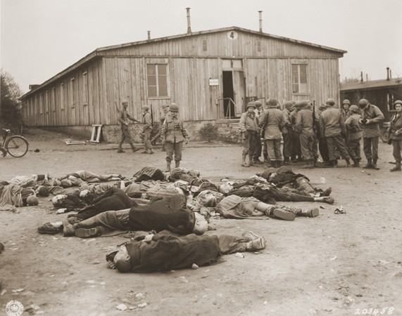 American soldiers view the bodies of prisoners found in the newly liberated Ohrdruf concentration camp. [LCID: 77443]