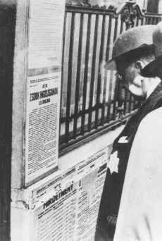 A Jewish man wearing a yellow star reads newly posted antisemitic regulations in Budapest. [LCID: 68612]