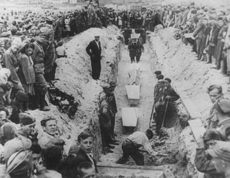 Mourners crowd around a narrow trench as coffins of pogrom victims are placed in a common grave, following mass burial service. [LCID: 85356]