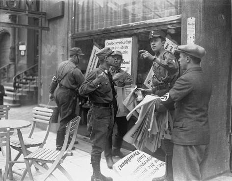 "<p>An SA member instructs others where to post <a href=""/narrative/102"">anti-Jewish boycott</a> signs on a commercial street in Germany. A German civilian wearing a Nazi armband holds a sheaf of anti-Jewish boycott signs, while SA members paste them on a Jewish-owned business. Most of the signs read, ""Germans defend yourselves against Jewish atrocity propaganda/Buy only at German stores."" Germany, ca. April 1, 1933.</p>"