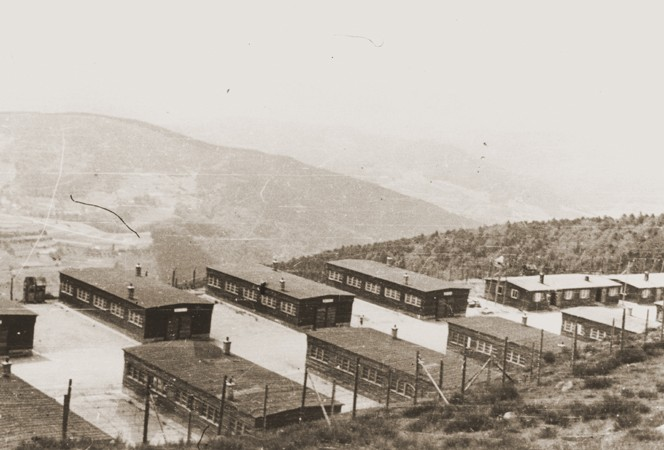 """<p>View of buildings in the <a href=""""/narrative/10581/en"""">Natzweiler</a> concentration camp. Beginning in the summer of 1943, the Germans detained many <a href=""""/narrative/11002/en"""">""""Night and Fog""""</a> prisoners in Natzweiler-Struthof. This photograph was taken following the liberation of the camp. Natzweiler-Struthof, France, 1945.</p>"""