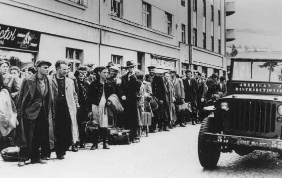 <p>Jewish refugees who fled Poland as part of the postwar mass flight of Jews from eastern Europe (the Brihah) line the streets outside a reception center. Nachod, Czechoslovakia, July 1946.</p>