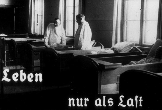 "<p>This photo originates from a film produced by the Reich <a href=""/narrative/11806/en"">Propaganda Ministry</a>. It shows two doctors in a ward in an unidentified asylum. The existence of the patients in the ward is described as ""life only as a burden."" Such <a href=""/narrative/81/en"">propaganda</a> images were intended to develop public sympathy for the <a href=""/narrative/4032/en"">Euthanasia Program</a>.</p>"