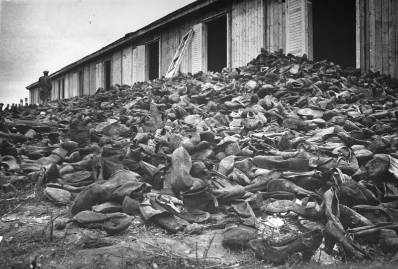 "<p>A Soviet soldier walks through a mound of victims' shoes piled outside a warehouse in <a href=""/narrative/3168"">Majdanek</a> soon after the <a href=""/narrative/2317"">liberation</a>. Majdanek, Poland, August 1944.</p>"