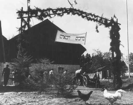 """<p><span lang=""""FR"""">Bannière de bienvenue au-dessus de l'entrée du kibboutz-hachshara de Buchenwald (coopérative agricole sioniste).</span></p>"""