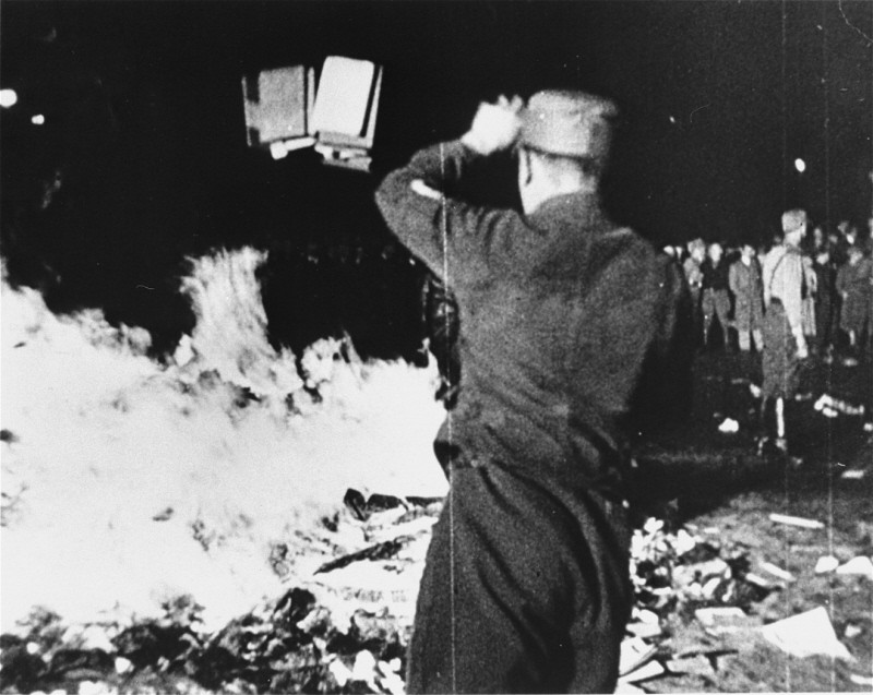 "At Berlin's Opernplatz, an SA man throws books into the flames at the public burning of books deemed ""un-German."" [LCID: 01622]"