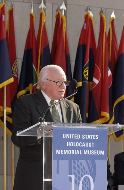 Standing in front of flags of the liberating divisions, Ben Meed, President, American Gathering of Jewish Holocaust Survivors, speaks at a ceremony held during the Museum's Tribute to Holocaust Survivors: Reunion of a Special Family, one of the Museum's tenth anniversary events.