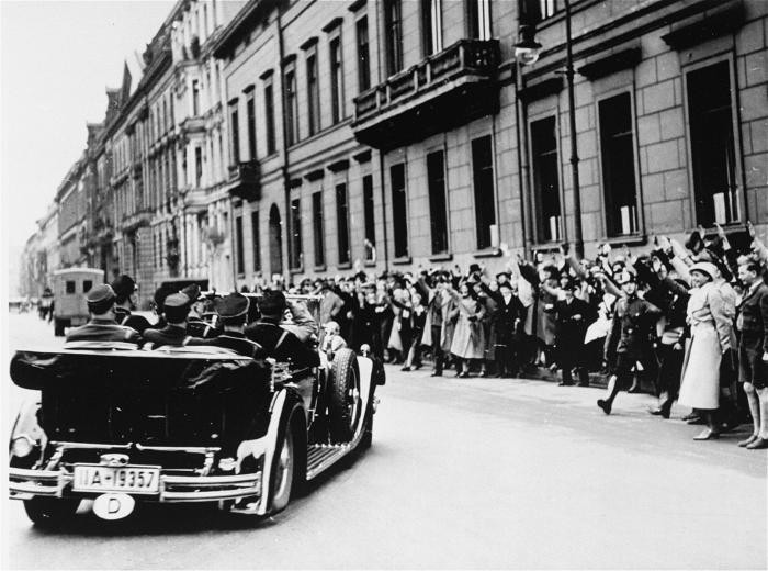 Spectators cheer as Hitler leaves for the Reichstag
