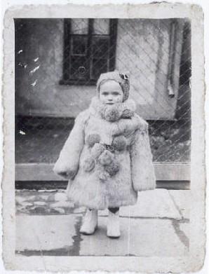 <p>صورة لإستيرا هورن وهي في الثالثة من عمرها ملتفة بمعطف من الفرو. كيلم، بولندا، سنة 1940 تقريبا. ولدت إستيرا في يناير عام 1937. وقد قُتل أبوها بعد غزو الألمان لبولندا مباشرة. لقد اضطرت إستيرا وأمها، بيرلا هورن، للترحيل إلى الحي اليهودي في كيلم. وفي نهاية عام 1942، خلال تصفية موقع جيتو، هربت بيرلا وإستيرا من جيتو. فقد اختبئتا في القرى المجاورة. وفي أواخر عام 1943، طلبت بيرلا من عائلة في بلاونس الاعتناء بإستيرا. لقد حاولت بيرلا أن تختبئ مع مجموعة من اليهود في الغابة المجاورة، إلا أن الألمان اكتشفوا مكان تواجدهم وقتلوهم. وفي ربيع عام 1944، بدأت العائلة في البحث عن منزل جديد لإستيرا (التي كانت تحمل اسم مارسيا). لقد عاشت في وارصوفيا وانتقلت في النهاية إلى دار للأيتام في كراكو.</p>