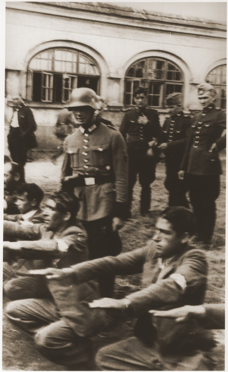 Members of the German Order Police publicly humiliate a group of Jews by forcing them to perform exercises, 1939–1940. Sosnowiec, in German-occupied Poland.