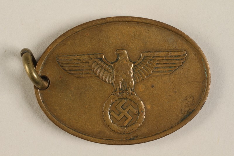 "<div class=""show-data"">Official identification tag (warrant badge) for the <a href=""/narrative/63226"">Criminal Police (<em>Kriminalpolizei</em> or Kripo)</a>, the detective police force of Nazi Germany. These badges were generally suspended from a chain and included the officer's identification number on the reverse.</div>"