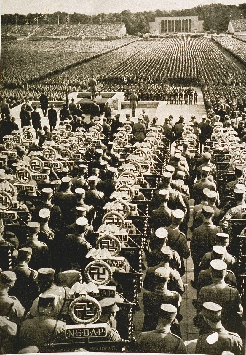 Rows of SA standard bearers line the field behind the speaker's podium at the 1935 Nazi Party Congress. [LCID: 07473]